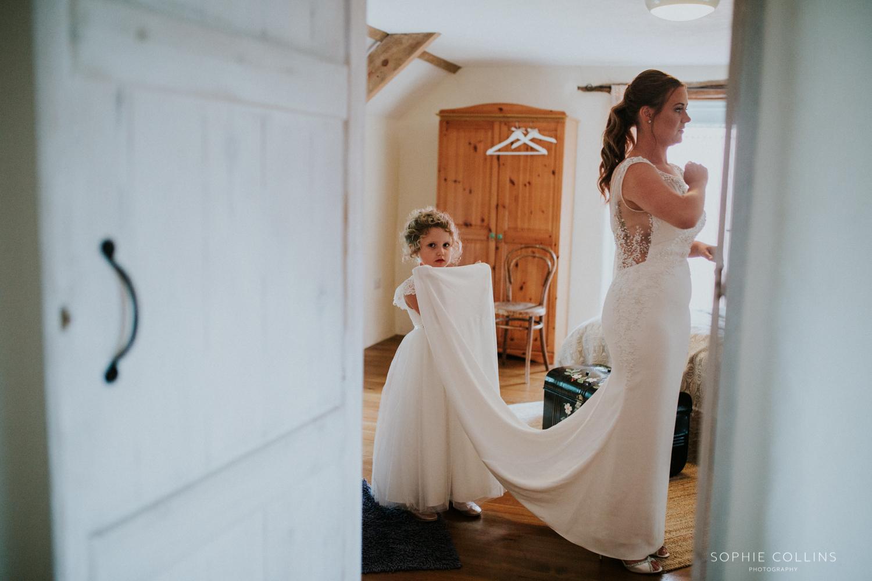 flower girl holding brides dress
