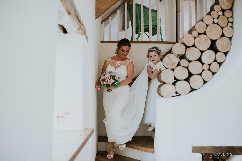 little girl holding brides dress