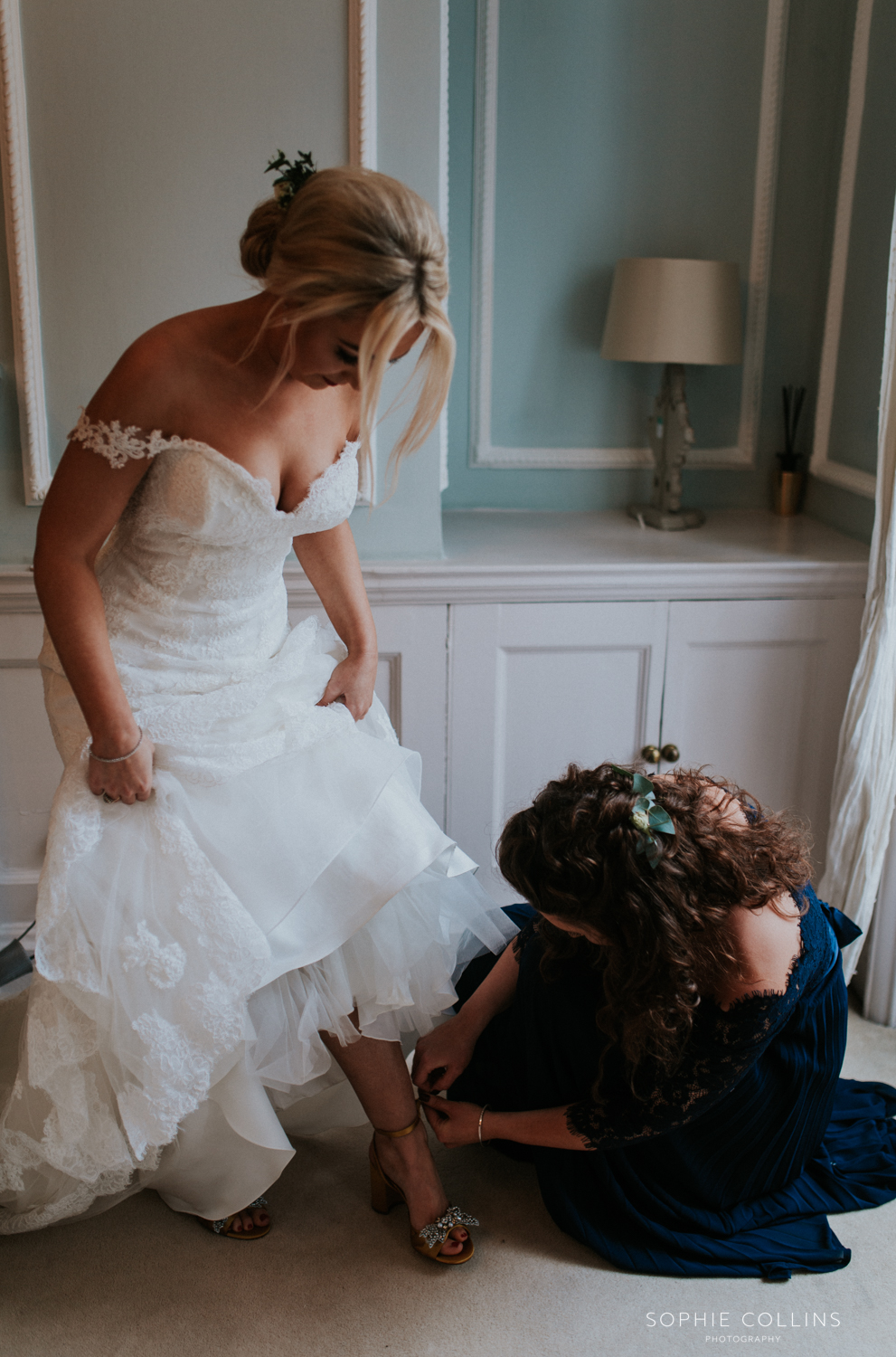 sister doing brides shoes